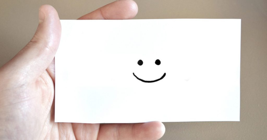 A hand holding a paper card with a drawn smiley face