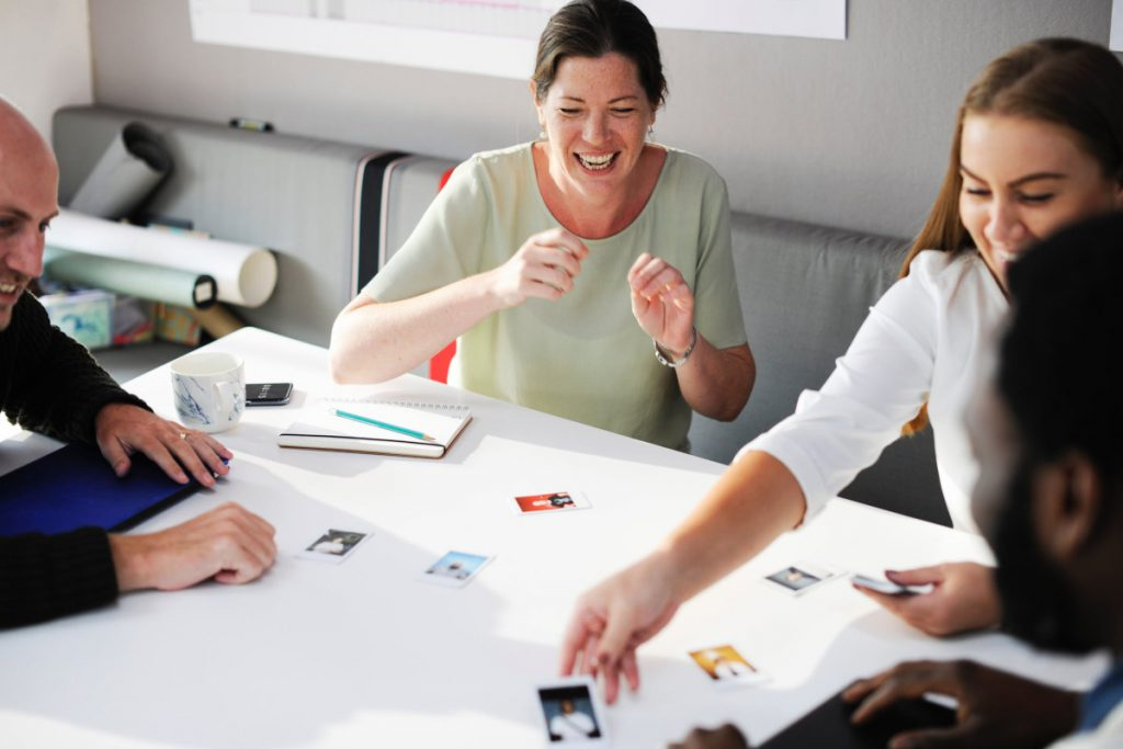 Team members playing a card game in an office space